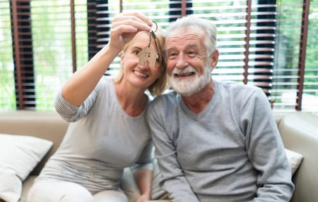 Love lives forever!  Happy Senior Couple are spending time together while sitting on sofa with keys in hands. Retirement couple Moving day Concept