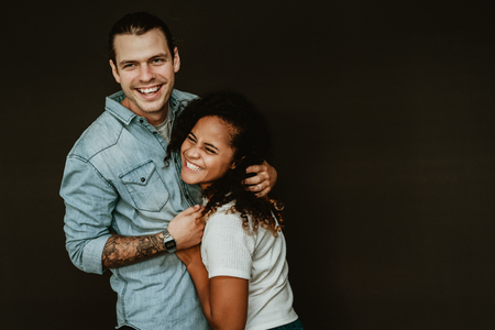 Portrait of happy excited mixed-race young couple in love hugging and having fun on the black background. Relationship concept with boyfriend and girlfriend together