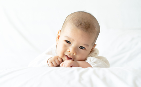 Nettes glückliches kleines Baby, das im weißen Bett lächelt. Neugeborenes Kind, das im Bett sich entspannt. Kindergarten für Kinder. Familie, neues Leben, Kindheit, Anfangskonzept.