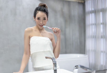 Young beautiful Asian woman brushing her teeth with a toothbrush in front of her bathroom mirror and looking at camera. Healthy teeth.