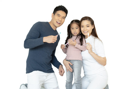 Portrait of smiling happy Asian family brushing teeth and smiling at camera isolated on white.Healthy teeth.