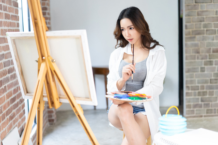 Female Asian artist in casual clothes holding palette and putting brush into paint in studio.Woman painter painting in her workshop.Creative concept Stock Photo
