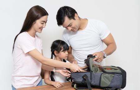 Familia multiétnica feliz ayudando a su hija a preparar la mochila escolar ir a la escuela. Familia feliz y estudiante de preescolar y educación.