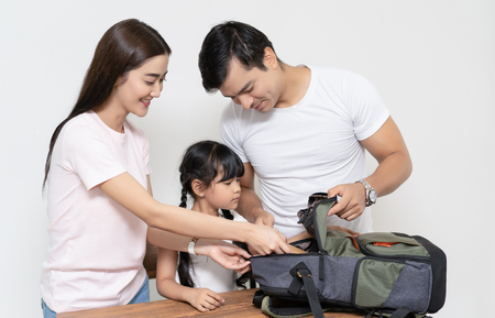 Happy multiethnic family helping daughter preparing school bag go to School.Happy family and preschool student and education.