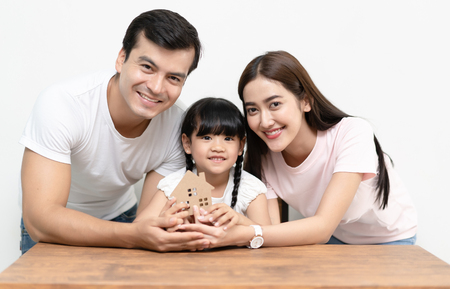 Happy multiethnic family holding paper house, family home, homeless housing and home protecting insurance concept. Moving house day and real estate concept