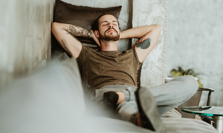 Portrait of young bearded man sleeping on the cozy modern sofa in light living room.Brutal bearded boy with tattoo.People and lifestyle Concept.