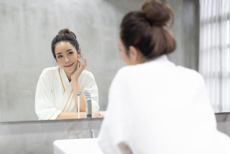 Belleza facial Hermosa mujer asiática joven sonriente en bata de baño aplicando crema humectante en su cara bonita y mirando al espejo en el baño, tocando la cara con las manos. Cuidado de la piel natural y concepto de personas. Foto de archivo