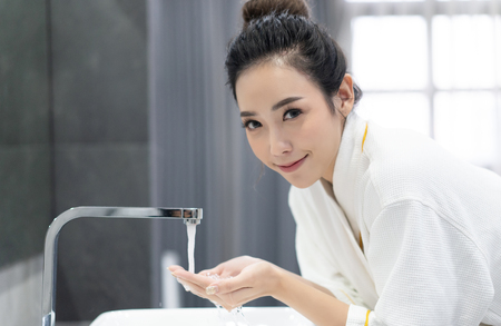 Beautiful Asian girl in bathrobe washing her face with water above bathroom sink and looking at camera and smiling in her bathroom.Natural skin care and people Concept. Banco de Imagens
