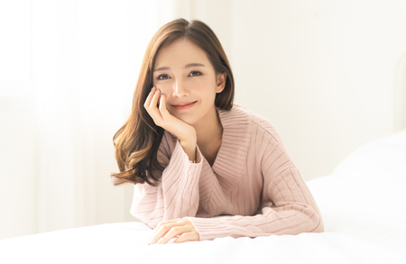 Portrait of young Asian woman smiling friendly and looking at camera in living room.Woman's face closeup. Concept woman lifestyle and winter. Autumn, winter season. Stok Fotoğraf