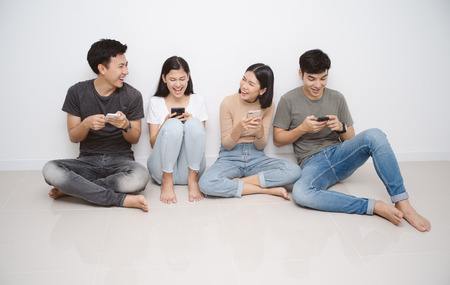 Group of friends sitting on the floor using smart mobile phones. People addiction to new technology trends. Concept of youth, z generation, social network and friendship.