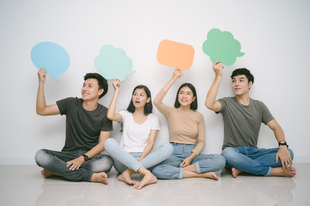 Group of friends sitting on the floor looking sideways while holding up speech bubble icons Imagens