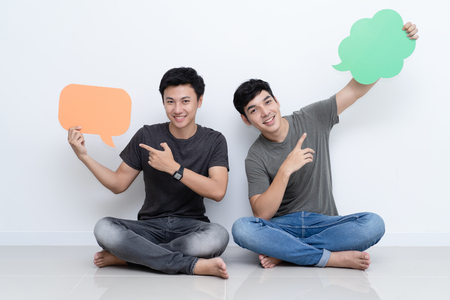 Male gay couple holding up speech bubble icons Imagens