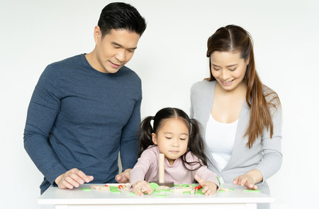 Mom, dad and girl playing together with wooden toys on white room.Daughter with unhappy with the parents after playing with her toys. Family and childhood concept.
