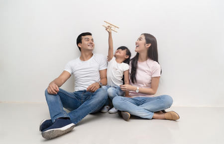 Happy multiethnic family sitting on the floor and playing toy airplane together. Family and childhood concept.