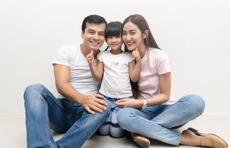 Portrait d'une famille multiethnique heureuse assise sur le sol avec des enfants et regardant la caméra. Concept de famille et d'enfance