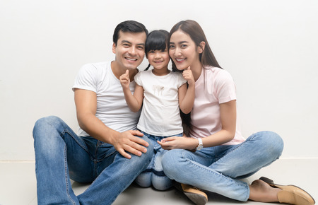 Portrait Of Happy multiethnic family sitting on floor with children and looking at camera. Family and childhood concept