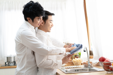 Young Asain happy male gay couple is washing dishes while doing cleaning  at kitchen.