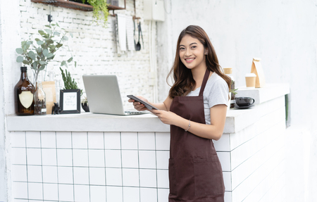 Portrait of a smiling young Asian barista in apron smiling using tablet and looking away on beside coffee machine in counter. Startup Business Owner Concept.SME Business Concept