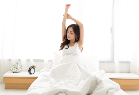 Young beautiful woman waking up happy after healthy sleep stretching on comfortable bed. Sweet dreams, good morning, new day, weekend, holidays concept
