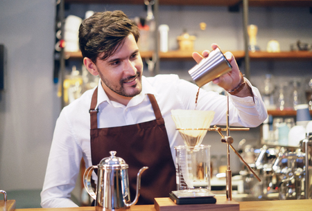 Barista young man pouring coffee into making drip coffee. Professional barista preparing coffee on counter. Startup Small Business owner concept. SME Business Concept.