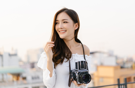Portrait of young Asian smiling woman model with retro film camera  and looking away on the rooftop of a building. Holiday lifestyle trip