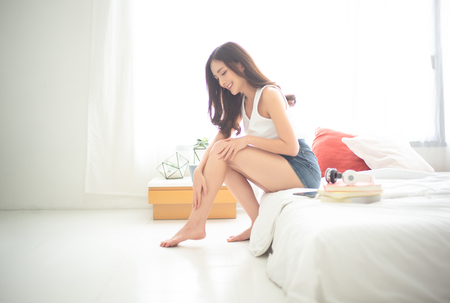Beautiful Asian woman sitting on bed and applying cream on legs. Beauty And Body Care Concept. 스톡 콘텐츠