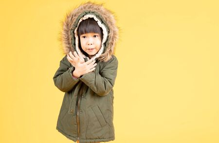 Little Asian girl wearing a fur hooded winter coat on the yellow background 免版税图像
