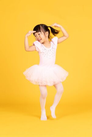 Cute ballerina little Asian girl in pink dancer over a yellow background. Kid in dance class. Child girl is studying ballet. Banco de Imagens