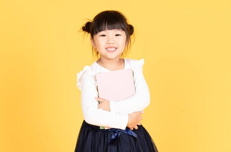 Portrait of cute little Asian girl while holding his school books and looking excited about going back to school isolated against yellow background. School and Education concept Banque d'images - 132043292