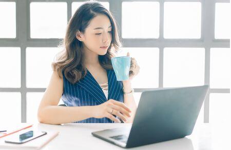Porträt der schönen asiatischen Geschäftsfrau, die nahe hellem Fenster beim Betrachten offener Laptop-Computer auf Tisch und mit Tasse Kaffee sitzt.