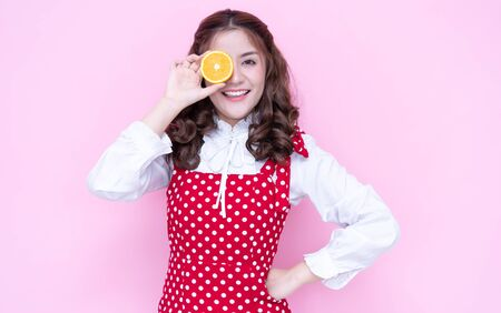 Portrait of a joyful attractive Asian woman holding orange one slices at her face and smiling on over pink background Stockfoto