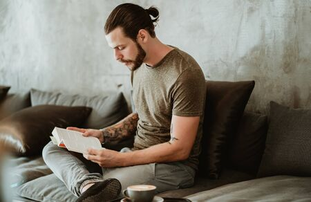 Portrait of young bearded hipster sitting in cafe while reading book and look aside.