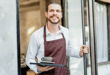 Portrait of bearded happy barista man working waitress in cafe open entrance door and serving drinks on a tray in front of the terrace cafe. Startup Small Business Owner Concept. SME Business Concept.