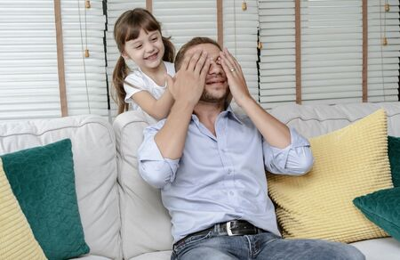 Happy family daughter covers her dads eyes while playing on holiday at living room