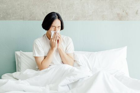 Sick young Asian man blowing his nose while sitting on bed at home.