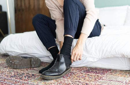 Close up of a young man is taking off his black patent leather boots at hotel