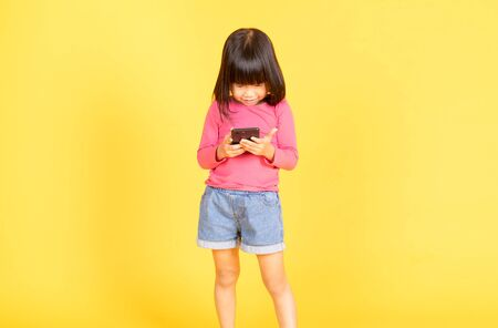 Curious little Asian girl playing games on her mobile phone isolated over yellow background.
