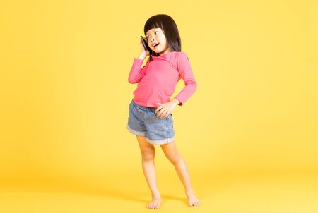 Portrait of a cute Asian little girl, talking on the phone, isolated on yellow background