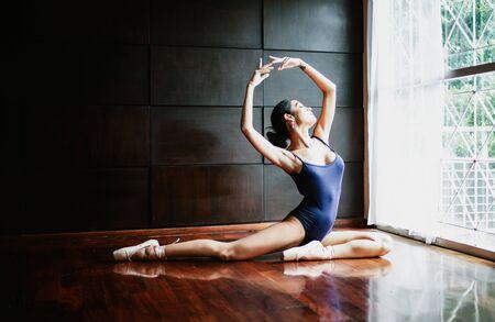 Beautiful Asian woman ballerina dancer in navy blue swimsuit posing in studio.