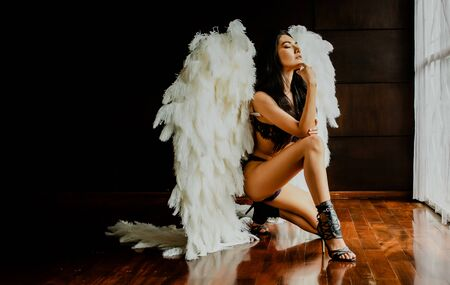 Portrait of beautiful sexy Asian woman with big angels wings sitting in her room.