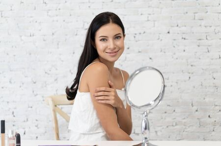 Portrait of a gorgeous young brunette woman fresh natural skin making make-up near mirror and looking at camera. Natural Makeup Touching Face. Cosmetic concept. Imagens - 132043762