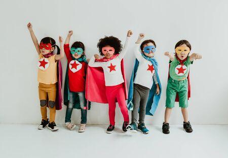 Gruppe von verschiedenen Kindern, die Superhelden auf dem weißen Wandhintergrund spielen. Superhelden-Konzept. Fröhliche Zeit. Standard-Bild