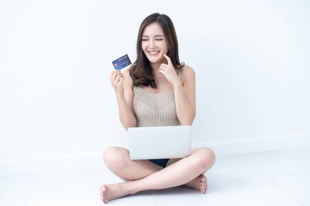 Happy young woman sitting on floor with credit card and using notebook while relaxing in the white room during free time. Internet bank, online shopping, technology and e-money concept