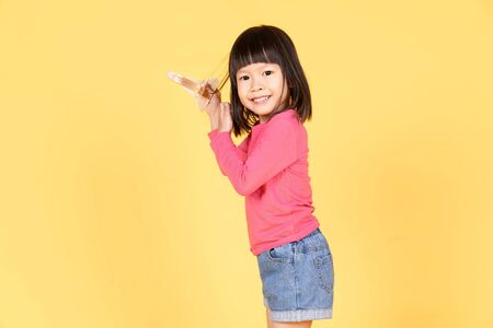 Happy asian girl playing with a toy airplane and looking at camera on yellow background isolated. Dreaming of becoming a pilot. 免版税图像