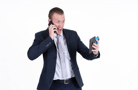 Portrait of young screaming businessman posing with four smartphones isolated over white wall background. Too many calls in one day. Stok Fotoğraf