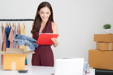 Portrait of young Asian casual woman working small business online packing jeans to cardboard box and check order in home office. Startup Small business owner,Online selling, e-commerce, SME Business,delivery, freelance working concept Foto de archivo - 132044061