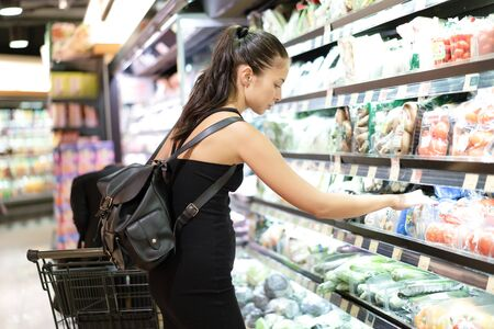 Enjoying shopping together. Beautiful women shopping vegetables and fruits in supermarket. Shopping, food, sale, consumerism and people concept
