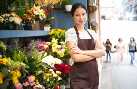 Young female business owner standing at her flower shop. Young entrepreneur leaning with her arms crossed and smiling confidently at the camera. Startup of small business owner and service mind concept. Stock fotó