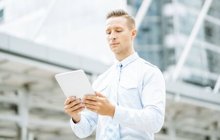 Young business man standing near office building and using a digital tablet. Mobile technology and communication Concept. Stok Fotoğraf