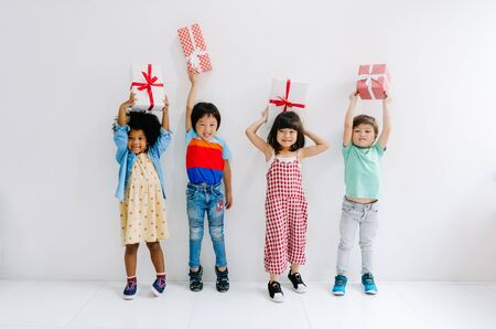 Group of adorable kids diverse cultures holding surprise gift boxes in party on the white wall background. Kids fashion and Celebration Concept.